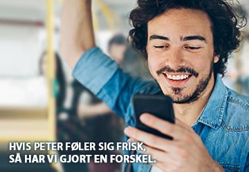 Sort håret mand i denim skjorte står og ser ned i sin telefon