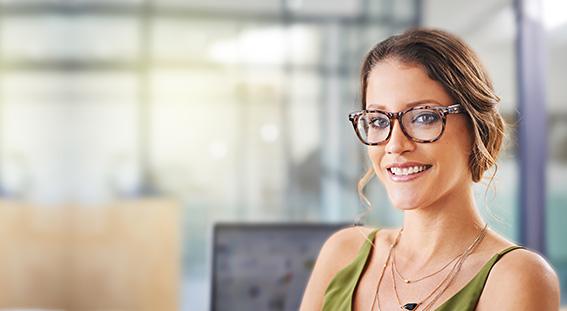 Voksen kvinde med briller og akne fri hud ser på kameraet