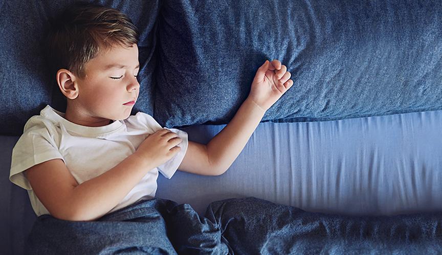Sovende mørkhåret dreng i hvid tshirt der klør sig på armen