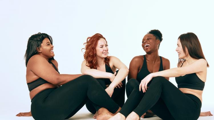 kvinder med forskellige hudfarver sidder på gulvet og griner