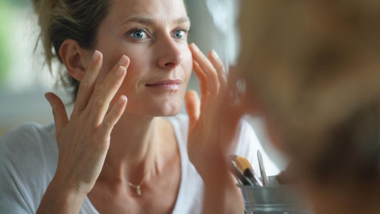 Kvinde der kigger sig selv i spejlet efter pigmentfejl og pigmentpletter