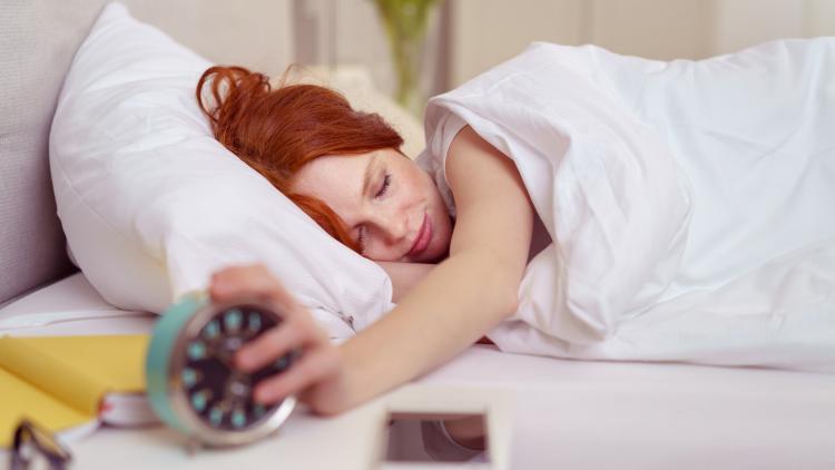 Sovende rødhåret kvinde rækker ud efter sit vække ur