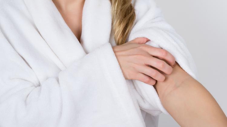 Kvinde i hvid badekåbe klør sin lidt røde arm